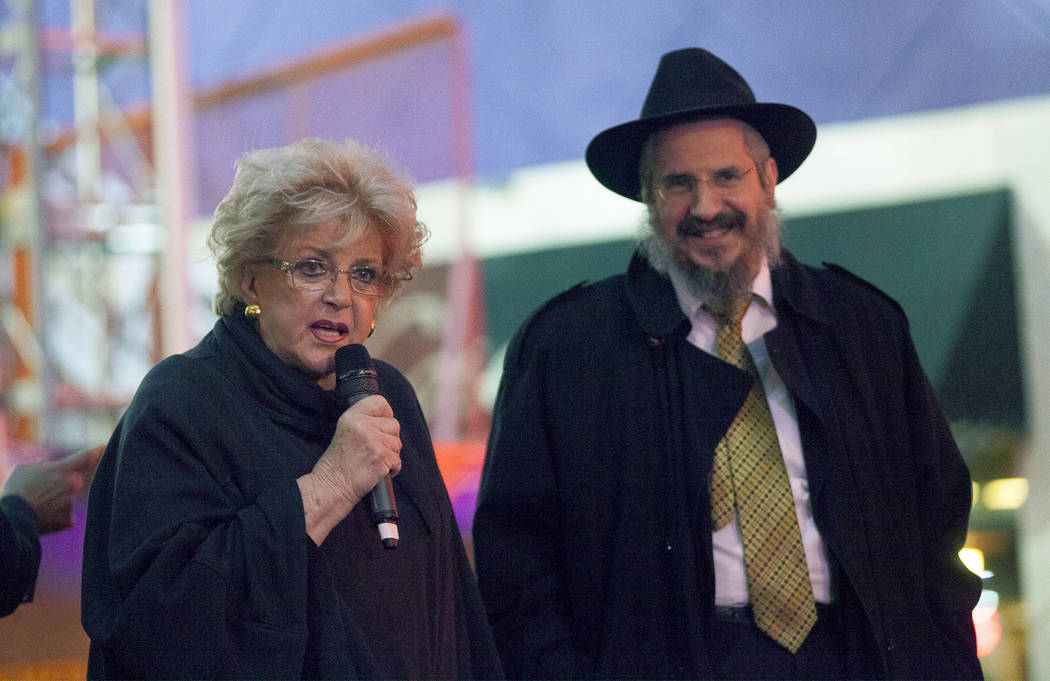 Mayor Carolyn Goldman addresses the crowd next to Rabbi Shea Harlig at the Grand Menorah lighting to celebrate the first day of Hanukkah at the Fremont Street Experience in Las Vegas, Sunday, Dec. ...