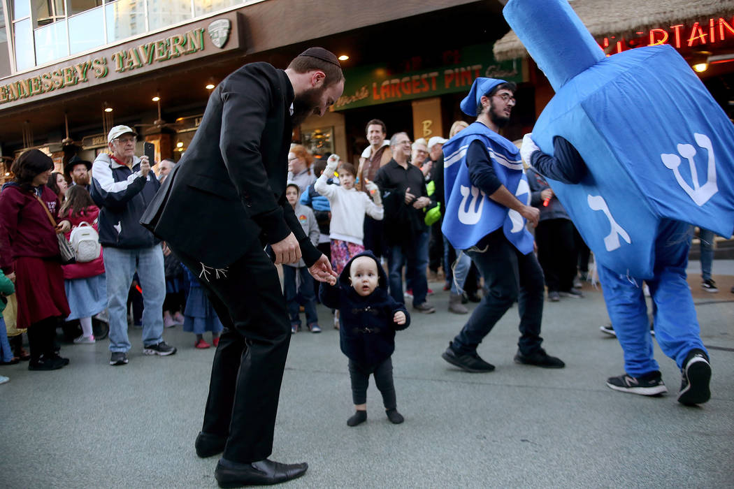 Rabbi Motti Harlig and his son Mendel Harlig, 1, dance with the Dancing Dreidels at the Grand Menorah lighting to celebrate the first day of Hanukkah at the Fremont Street Experience in Las Vegas, ...