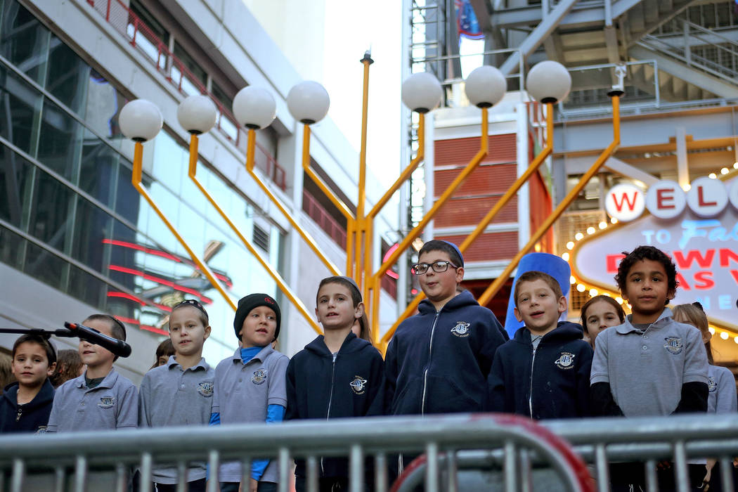 The Desert Torah Academy choir sings for the crowd at the Grand Menorah lighting to celebrate the first day of Hanukkah at the Fremont Street Experience in Las Vegas, Sunday, Dec. 2, 2018. Rachel ...