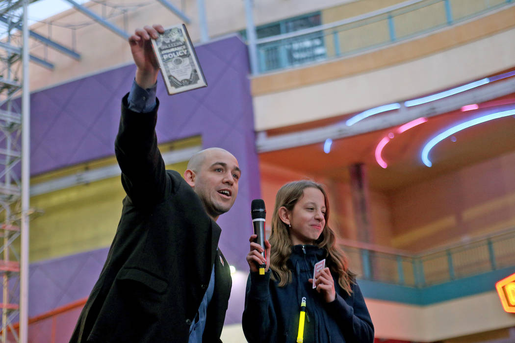 Magician Michael Mayfield does a trick with Chana Borsody, 11, at the Grand Menorah lighting to celebrate the first day of Hanukkah at the Fremont Street Experience in Las Vegas, Sunday, Dec. 2, 2 ...