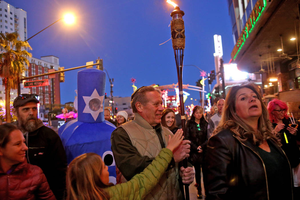 Richard Niederman walks through the crowd with a torch that will light the menorah at the Grand Menorah lighting to celebrate the first day of Hanukkah at the Fremont Street Experience in Las Vega ...