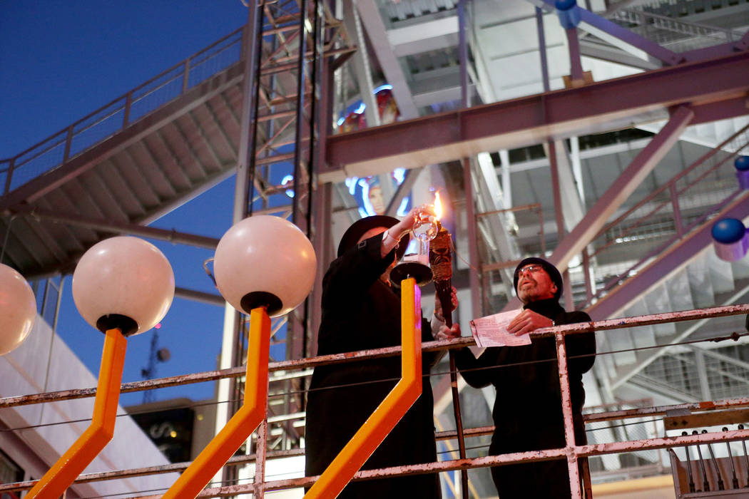 Rabbi Shea Harlig, left, lights the candle for the Grand Menorah alongside Bernie Yuman, who says the blessing, at the lighting ceremony to celebrate the first day of Hanukkah at the Fremont Stree ...