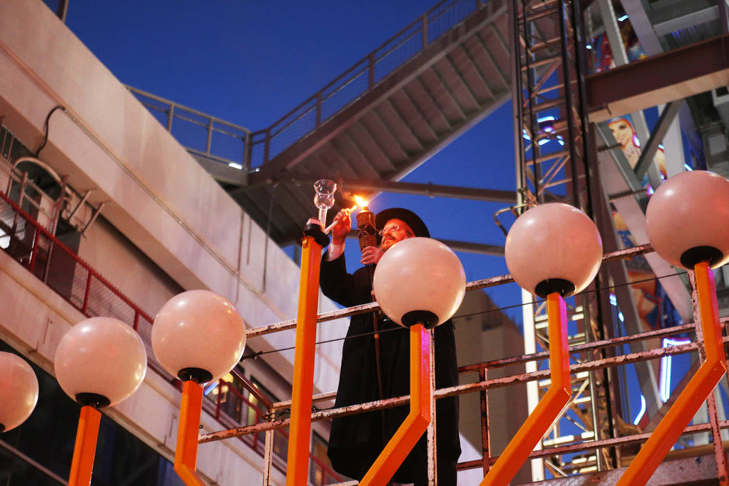 Rabbi Shea Harlig lights the shamesh candle that's used to light the other candles on the Grand Menorah at the lighting ceremony to celebrate the first day of Hanukkah at the Fremont Street Experi ...