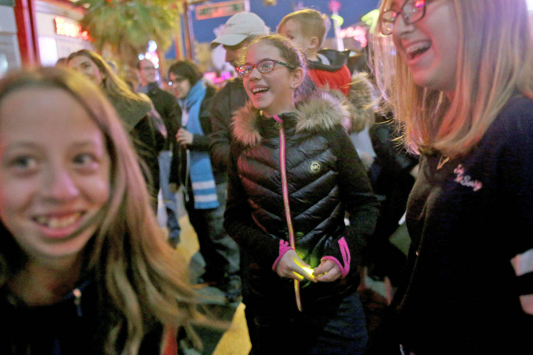 Chana Borsody, 12, from left, Adeena Sudranksi, 10, and Sarah Mowery, 13, laugh at the Grand Menorah lighting to celebrate the first day of Hanukkah at the Fremont Street Experience in Las Vegas, ...