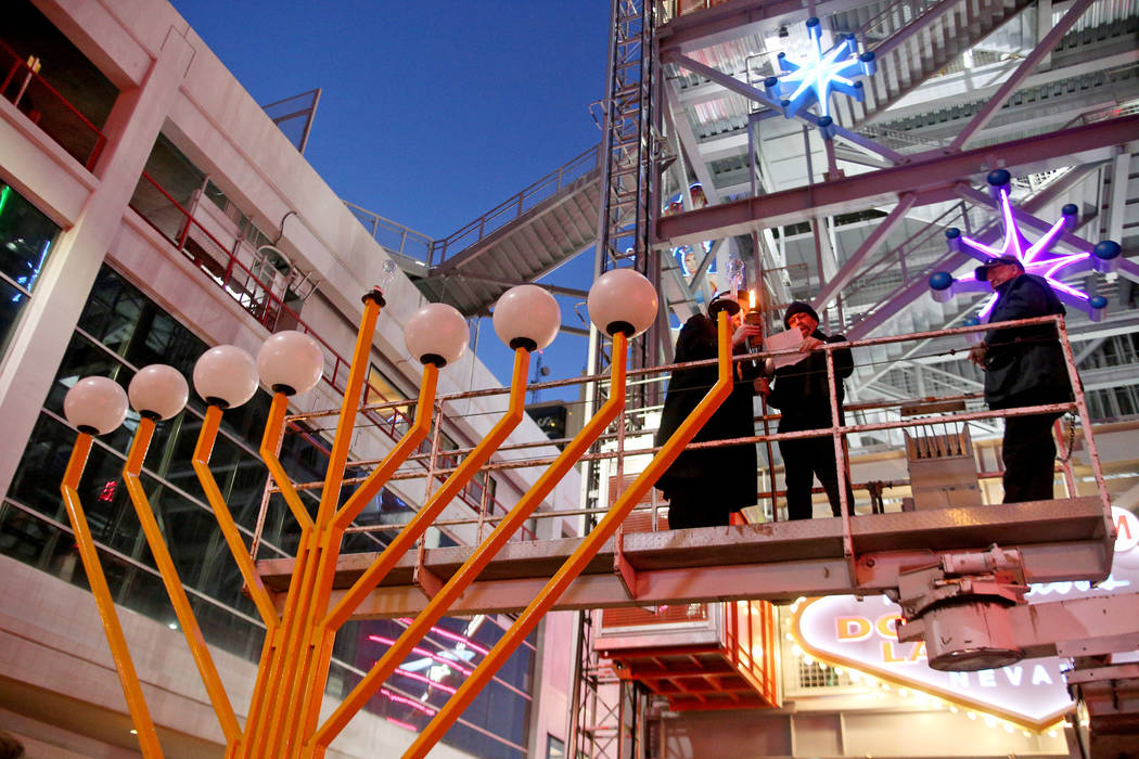 Rabbi Shea Harlig, left, holds the torch for the Grand Menorah alongside Bernie Yuman as he says the blessing at the lighting ceremony to celebrate the first day of Hanukkah at the Fremont Street ...