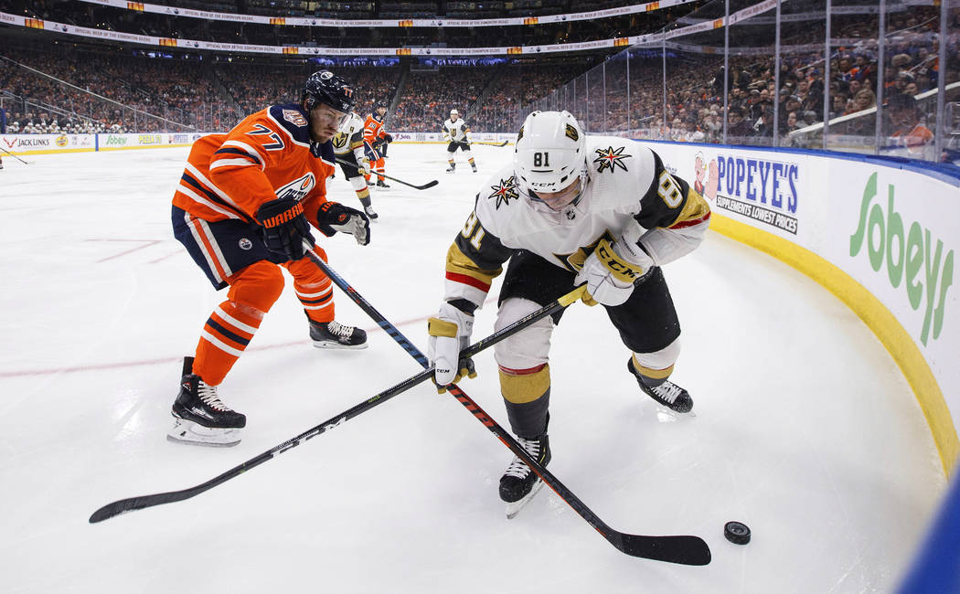 Vegas Golden Knights' Jonathan Marchessault (81) and Edmonton Oilers' Oscar Klefbom (77) compete for the puck during the first period of an NHL hockey game Saturday, Dec. 10, 2018, in Edmonton, Al ...