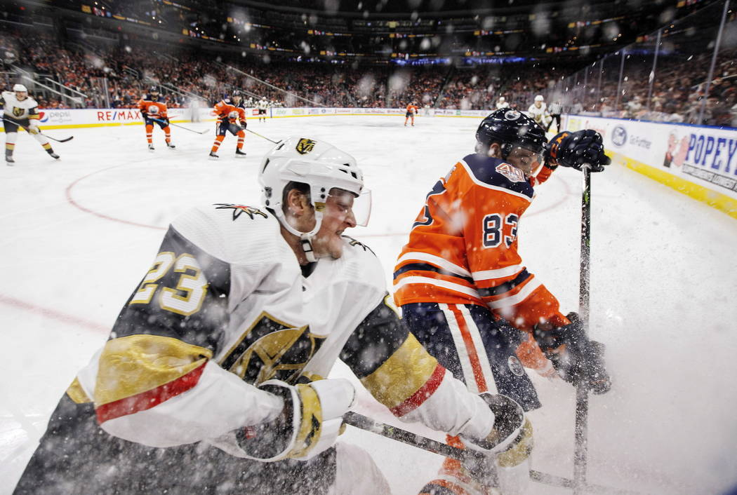 Vegas Golden Knights' Daniel Carr (23) and Edmonton Oilers' Matthew Benning (83) battle for the puck during the third period of an NHL hockey game Saturday, Dec. 1, 2018, in Edmonton, Alberta. (Ja ...