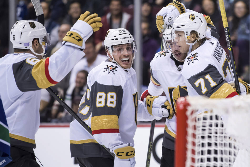 Vegas Golden Knights' Colin Miller, Nate Schmidt, Reilly Smith and William Karlsson, of Sweden, from left, celebrate Karlsson's goal against the Vancouver Canucks during the third period of an NHL ...