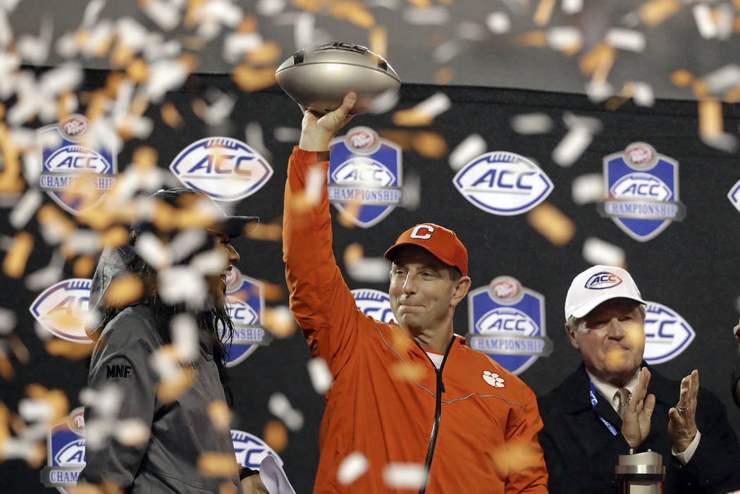 Clemson head coach Dabo Swinney raises the trophy after Clemson won the Atlantic Coast Conference championship NCAA college football game against Pittsburgh in Charlotte, N.C., Saturday, Dec. 1, 2 ...
