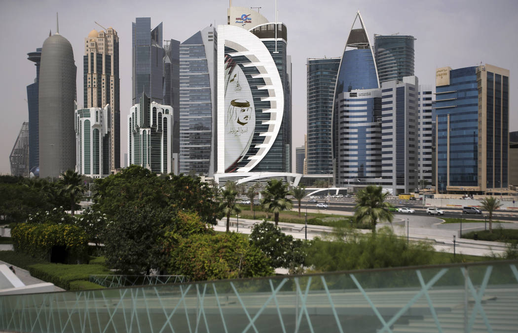 In this May 5, 2018, file photo, a giant image of the Emir of Qatar Sheikh Tamim bin Hamad Al Thani, adorns a tower in Doha, Qatar. The tiny, energy-rich Arab nation of Qatar announced on Monday, ...