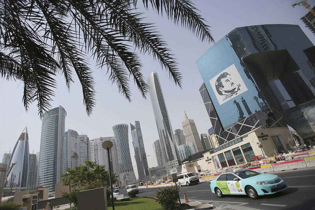 In this May 5, 2018, file photo, a taxi passes by a building with an image of emir of Qatar, Sheikh Tamim bin Hamad Al Thani, in Doha, Qatar. The tiny, energy-rich Arab nation of Qatar announced o ...