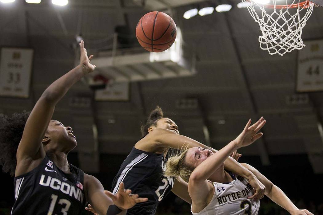 Connecticut's Olivia Nelson-Ododa (20) blocks a shot by Notre Dame's Marina Mabrey (3) next to Connecticut's Christyn Williams (13) during the second half of an NCAA college basketball game Sunday ...