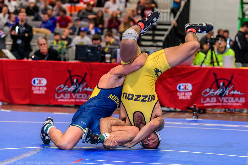 Michigan's Amine Brighton and Missouri's Daniel Lewis grapple for position during the 174-pound finals of the Cliff Keen Invitational college wrestling tournament at the Las Vegas Convention Cente ...