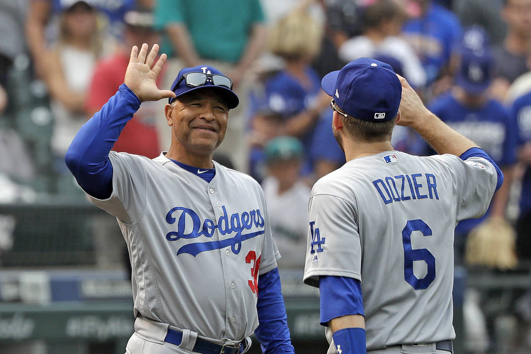 In this Aug. 19, 2018, file photo, Los Angeles Dodgers manager Dave Roberts, left, smiles as he greets Brian Dozier after they defeated the Seattle Mariners in a baseball game, in Seattle. (AP Pho ...