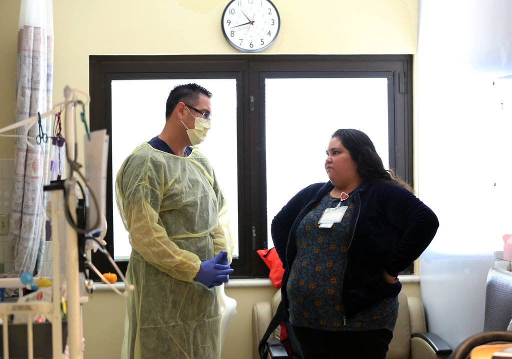 Dr. Oscar Ingaramo, left, Sunrise Children's Hospital PICU Medical director, discusses with Vanessa Macias, about hers son's condition on Monday, Dec. 3, 2018, at Sunrise Children's Hospital in La ...