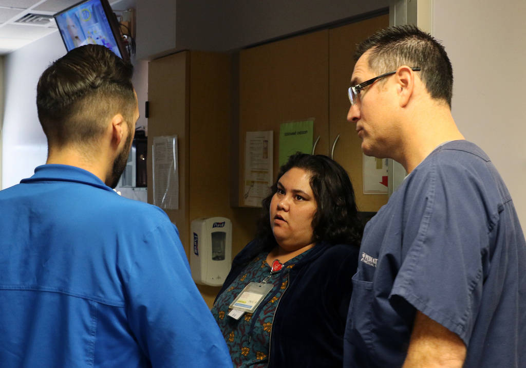 Dr. Oscar Ingaramo, right, Sunrise Children's Hospital PICU Medical director, and Arthur Ludice, nurse manager, discuss with Vanessa Macias, center, about hers son's condition on Monday, Dec. 3, 2 ...