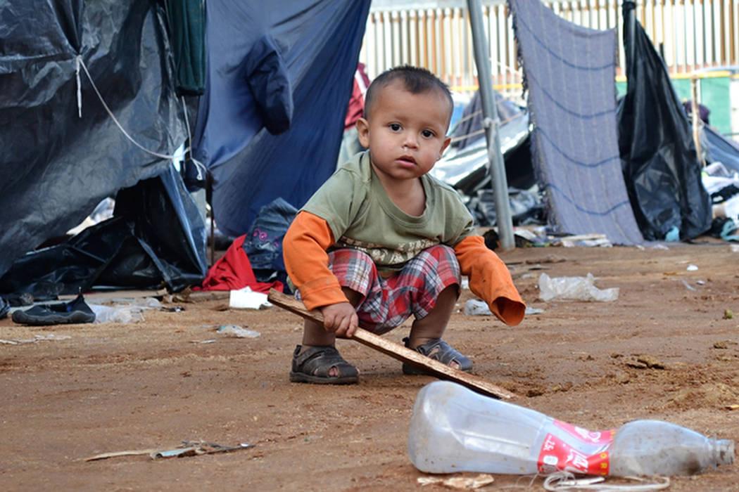 A toddler plays in the mud at a migrant encampment in Tijuana. (Doug Kari/Special to Las Vegas Review-Journal)