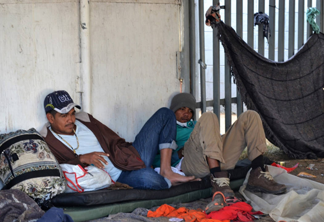 Migrant men on Friday, after a long night of rainfall. (Doug Kari/Special to Las Vegas Review-Journal)