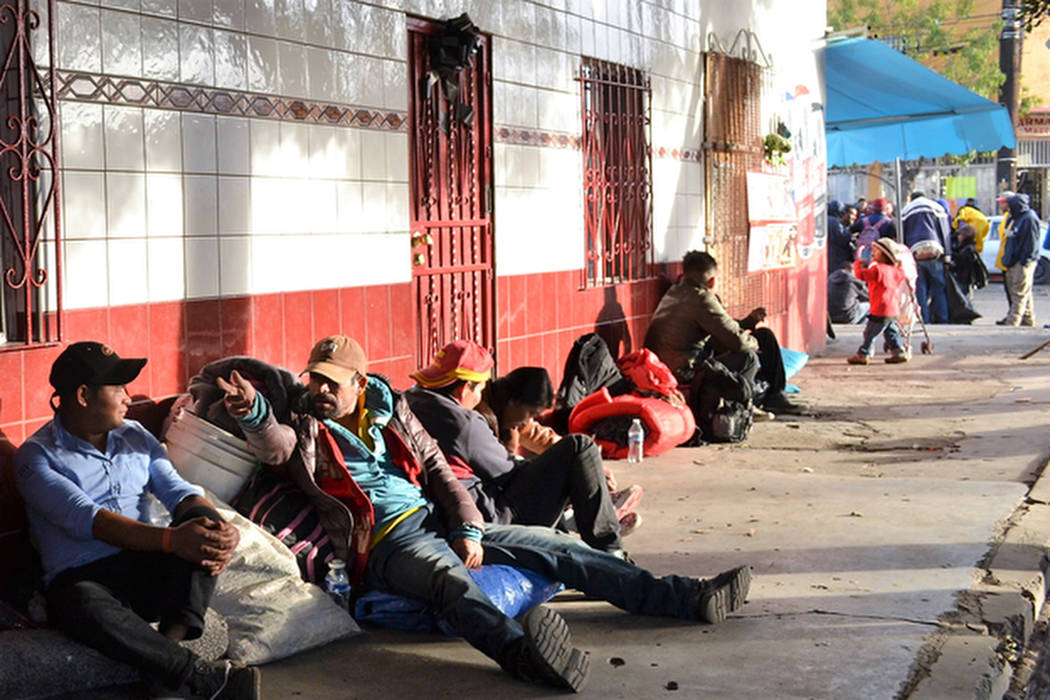 Men wait to be bused to the El Barretal migrant shelter in Tijuana. (Doug Kari/Special to Las Vegas Review-Journal)