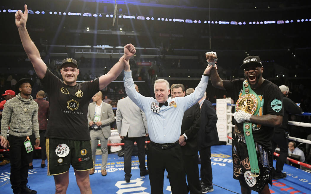 Tyson Fury, left, of England, poses with Deontay Wilder, right, along with referee Jack Reiss after their WBC heavyweight championship boxing match ended in a draw, Saturday, Dec. 1, 2018, in Los ...