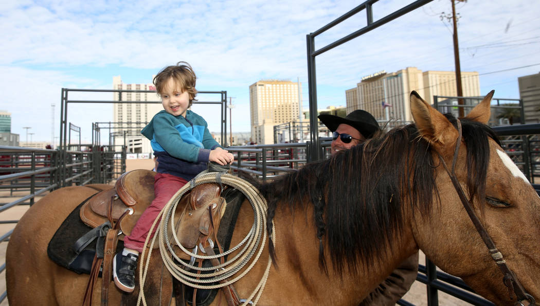 Noah Jossel, 2, son of Plaza CEO Jonathan Jossel, mounts a horse with the help of pickup rider Jared Groen, right, after the opening of Core Arena at the Plaza in downtown Las Vegas Tuesday, Dec. ...