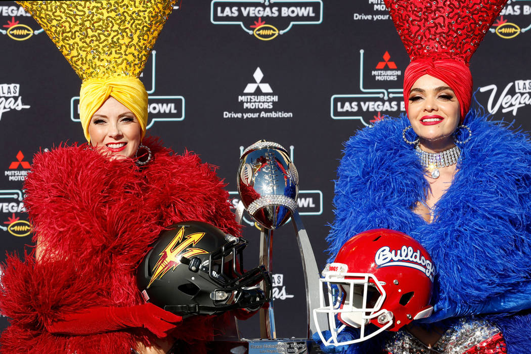 Showgirls Jennifer Autry, left, holding an Arizona State football helmet and Porsha Revesz holding a Fresno State helmet pose for a photo during a news conference in Las Vegas, Sunday, Dec. 2, 201 ...