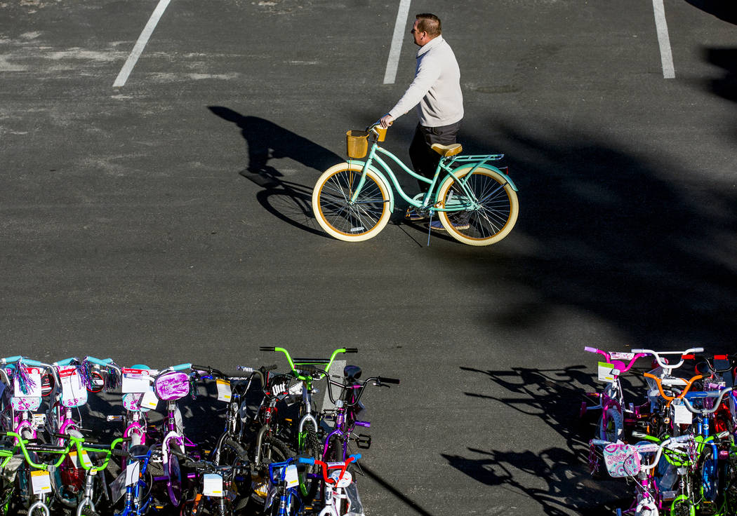 A man pushes a donated bicycle during the 18th Annual Chet Buchanan & The Morning Zoo Toy Drive outside Nevada Energy, 6226 W. Sahara Ave, on Thursday, Dec. 08, 2016. Jeff Scheid/Las Vegas Rev ...