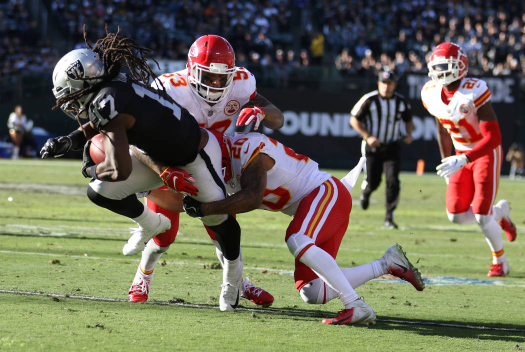 Oakland Raiders wide receiver Dwayne Harris (17) is tackled by Kansas City Chiefs cornerback Steven Nelson (20) and inside linebacker Anthony Hitchens (53) during the first half of an NFL game in ...