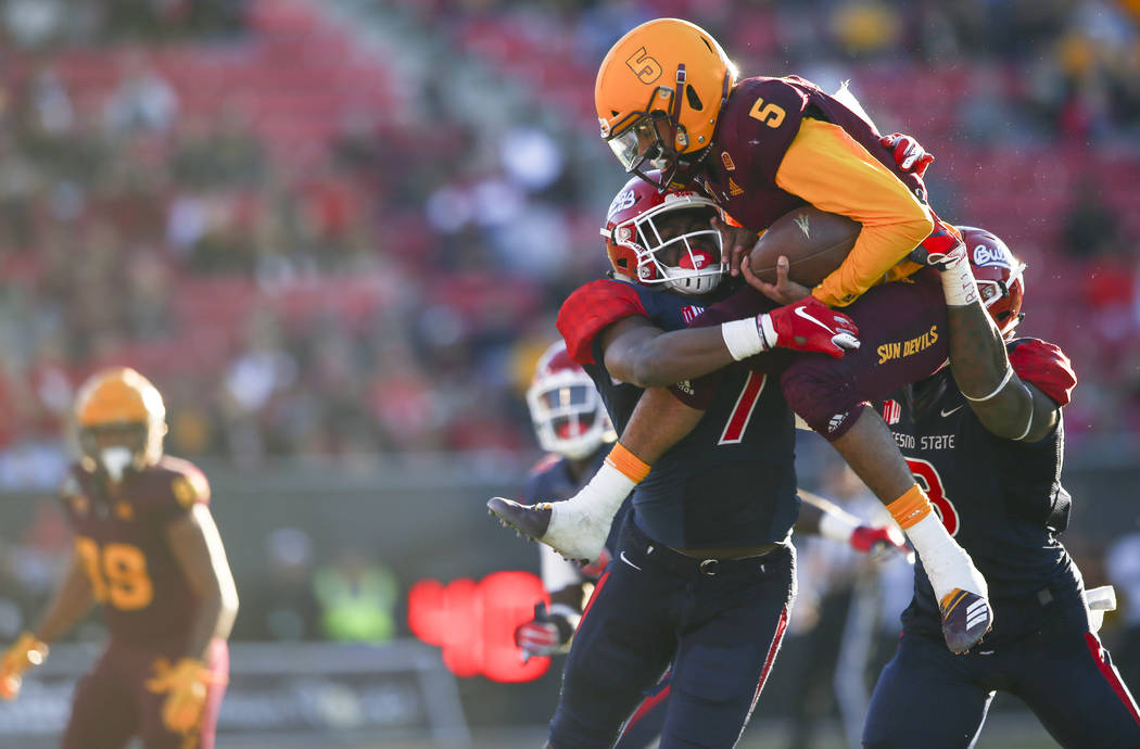 Arizona State quarterback Manny Wilkins (5) is stopped by Fresno State linebacker James Bailey (7) and defensive end Mykal Walker (3) during the second half of the Las Vegas Bowl football game at ...