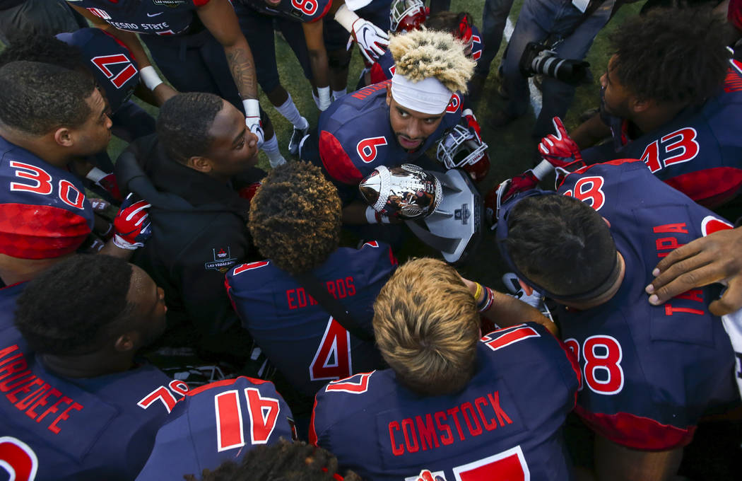 Fresno State quarterback Marcus McMaryion (6) holds the trophy as the team huddles in celebration of their win over Arizona State in the Las Vegas Bowl football game at Sam Boyd Stadium in Las Veg ...
