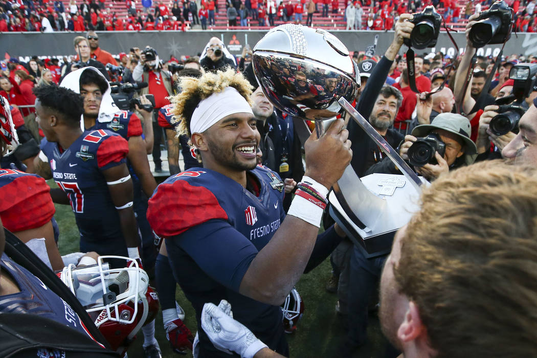 Fresno State quarterback Marcus McMaryion raises the trophy in celebration of his team's win over Arizona State of the Las Vegas Bowl football game at Sam Boyd Stadium in Las Vegas on Saturday, De ...