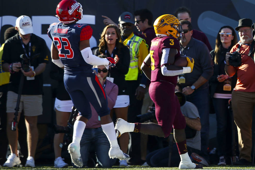 Arizona State running back Eno Benjamin (3) scores a touchdown past Fresno State defensive back Juju Hughes (23) during the first half of the Las Vegas Bowl football game at Sam Boyd Stadium in La ...