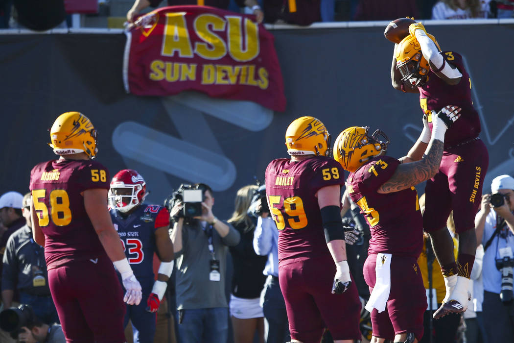 Arizona State offensive lineman Cohl Cabral (73) celebrates a touchdown by Arizona State running back Eno Benjamin (3) during the first half of the Las Vegas Bowl football game against Fresno Stat ...