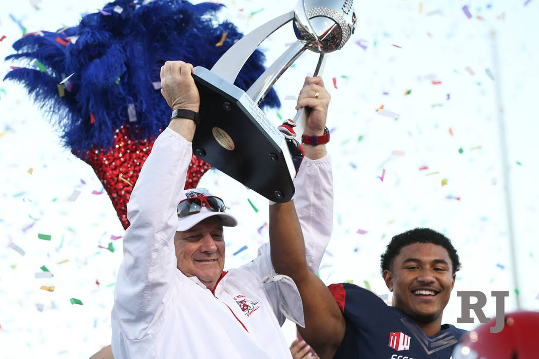 Fresno State head coach Jeff Tedford and running back Ronnie Rivers raise the trophy in celebration of their team's win over Arizona State of the Las Vegas Bowl football game at Sam Boyd Stadium i ...