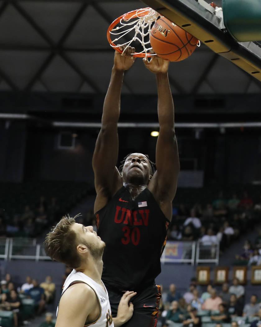 UNLV forward Jonathan Tchamwa Tchatchoua (30) slam dunks the ball over Hawaii forward Owen Hulland (15) during the first half of an NCAA college basketball game at the Diamond Head Classic, Saturd ...