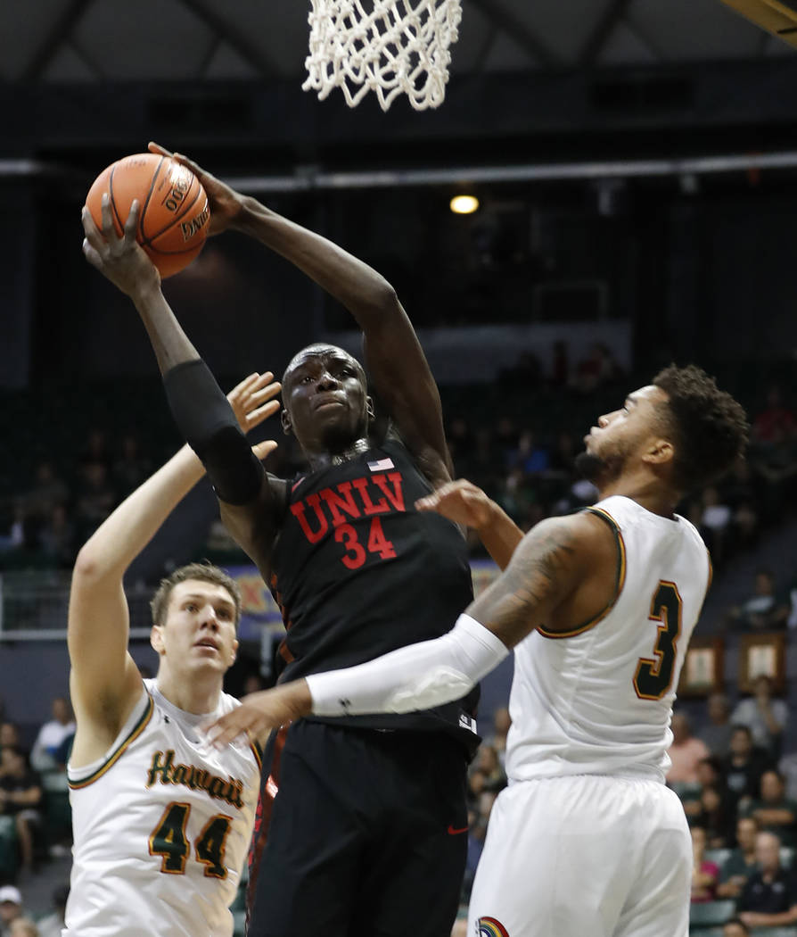 UNLV forward Cheikh Mbacke Diong (34) tries to shoot over Hawaii center Dawson Carper (44) and guard Eddie Stansberry (3) during the first half of an NCAA college basketball game at the Diamond He ...