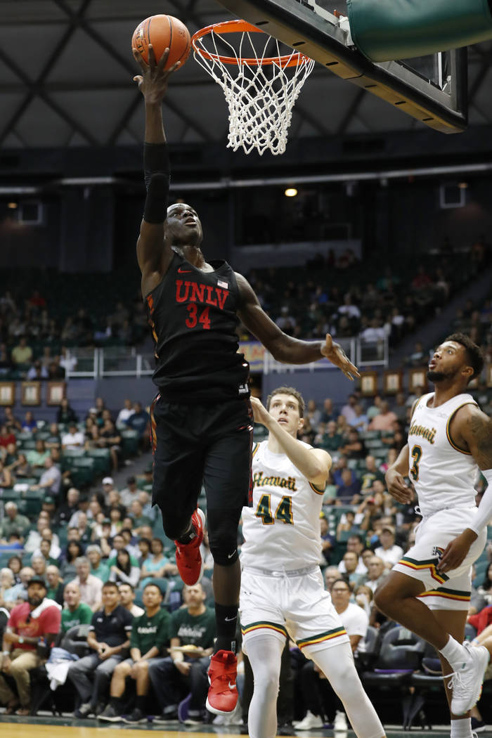 UNLV forward Cheikh Mbacke Diong (34) goes for the basket over Hawaii center Dawson Carper (44) and guard Eddie Stansberry (3) during the first half of an NCAA college basketball game at the Diamo ...