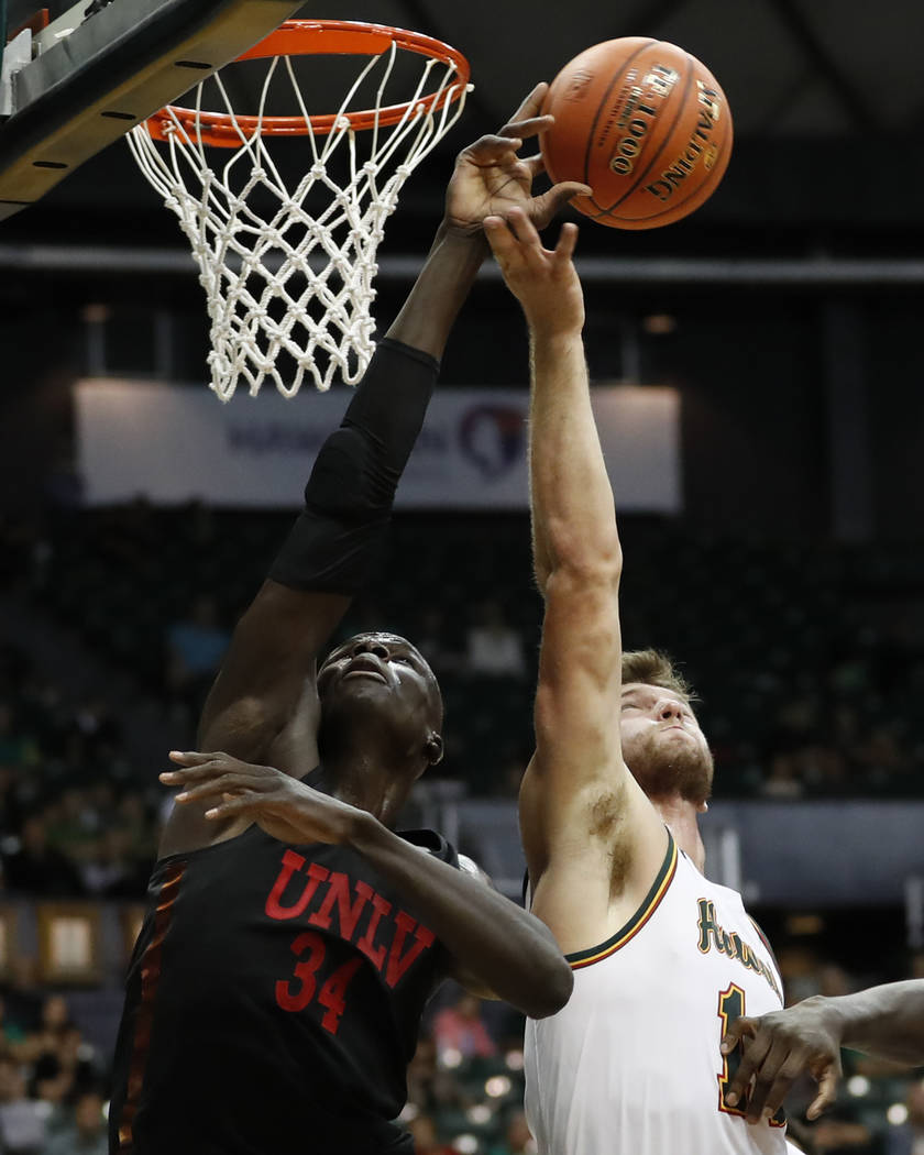 UNLV forward Cheikh Mbacke Diong (34) and Hawaii forward Zigmars Raimo (14) both try for a rebound during the first half of an NCAA college basketball game at the Diamond Head Classic, Saturday, D ...