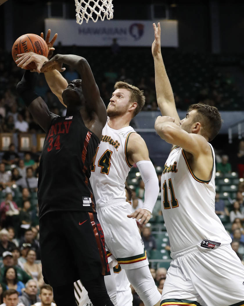Hawaii forward Zigmars Raimo (14) fouls UNLV forward Cheikh Mbacke Diong (34) as Hawaii center Mate Colina (11) guards during the first half of an NCAA college basketball game at the Diamond Head ...