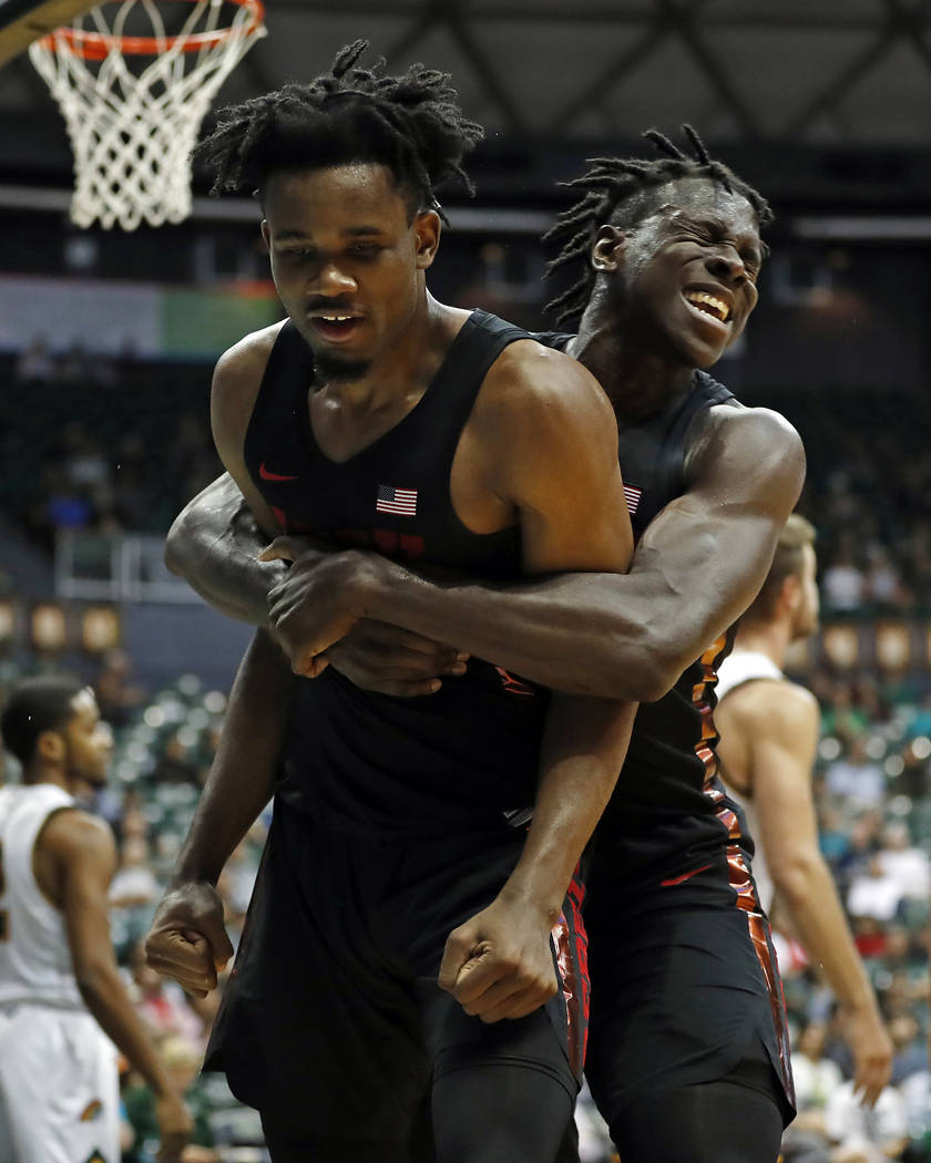 UNLV forward Joel Ntambwe (24) celebrates with forward Jonathan Tchamwa Tchatchoua (30) after he made a basket and drew a foul against Hawaii during the second half of an NCAA college basketball g ...