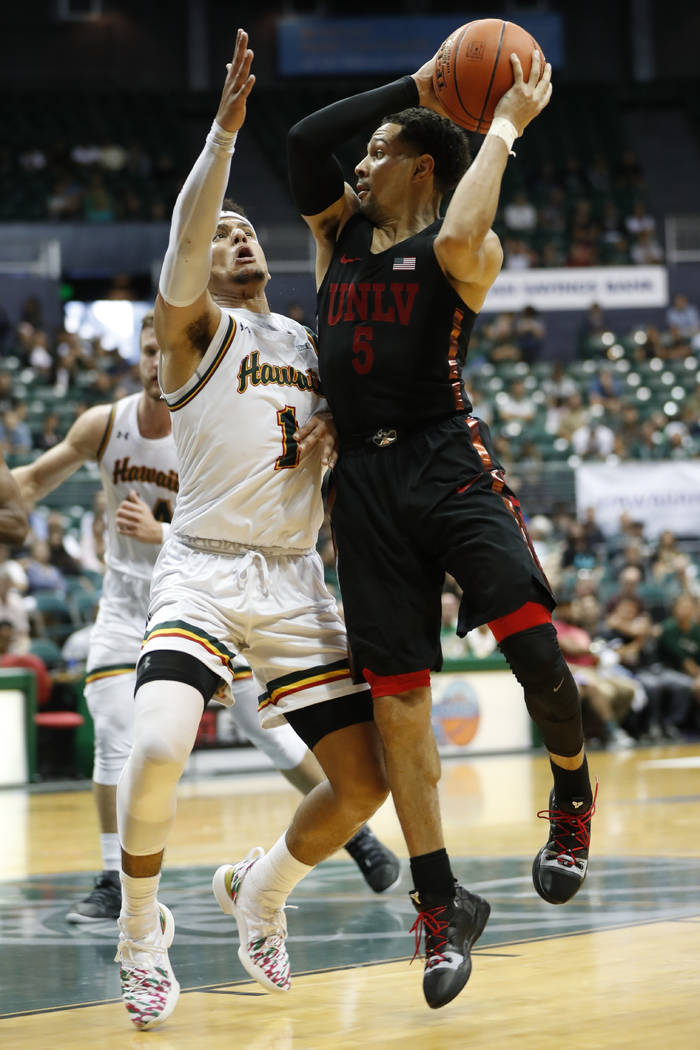 UNLV guard Noah Robotham (5) looks to pass the ball over Hawaii guard Drew Buggs (1) during the second half of an NCAA college basketball game at the Diamond Head Classic, Saturday, Dec. 22, 2018, ...