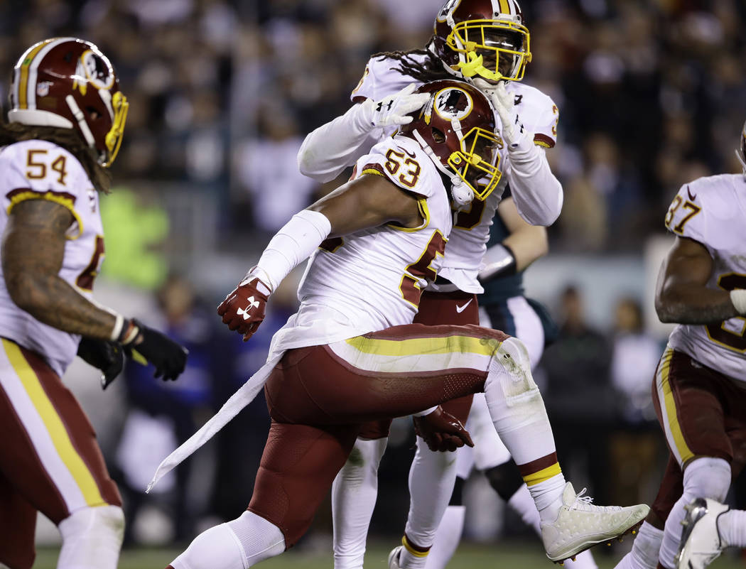 Washington Redskins' Zach Brown (53) is congratulated by teammates after making a tackle on fourth down during the first half of an NFL football game against the Philadelphia Eagles, Monday, Dec. ...