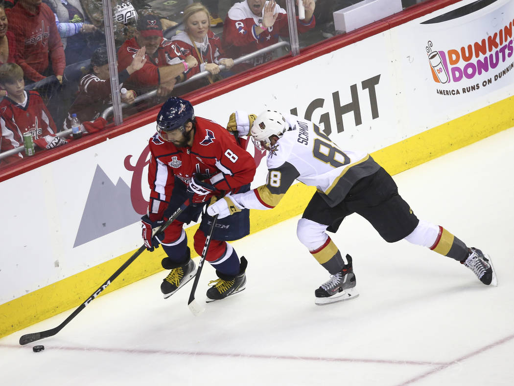 Washington Capitals left wing Alex Ovechkin (8) moves the puck as Golden Knights defenseman Nate Schmidt (88) defends during the first period of Game 3 of the NHL hockey Stanley Cup Final at Capit ...