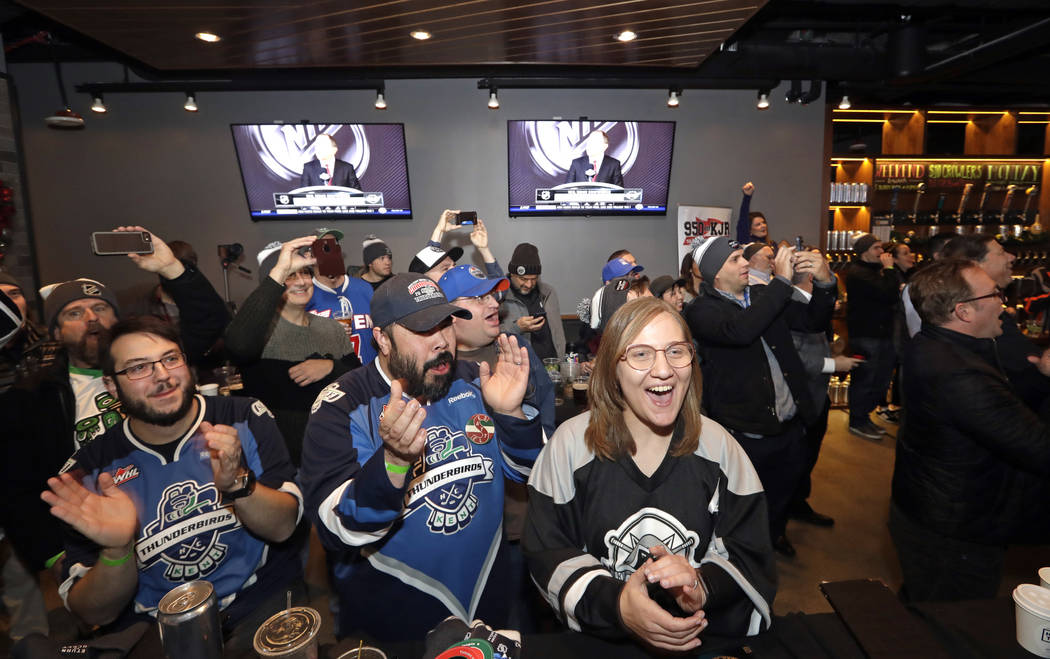 Hockey fans cheer the announcement of a new NHL hockey team in Seattle at a celebratory party Tuesday, Dec. 4, 2018, in Seattle. The NHL Board of Governors unanimously approved adding Seattle as t ...