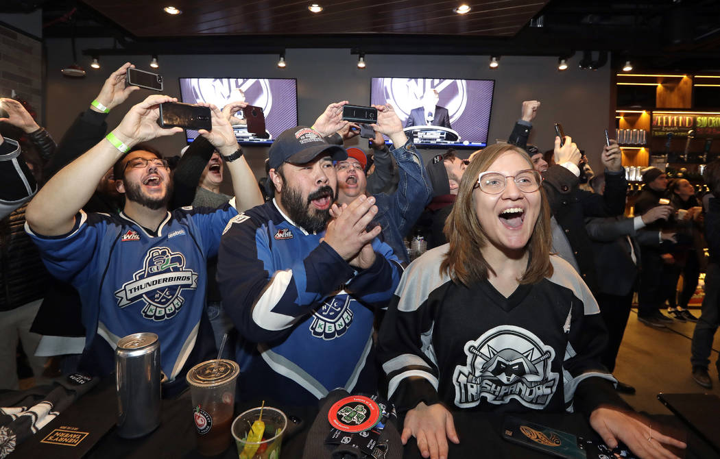 Ryan Kelly, left, Otto Rogers and Rebecca Moloney cheer the announcement of a new NHL hockey team in Seattle at a celebratory party Tuesday, Dec. 4, 2018, in Seattle. The NHL Board of Governors un ...