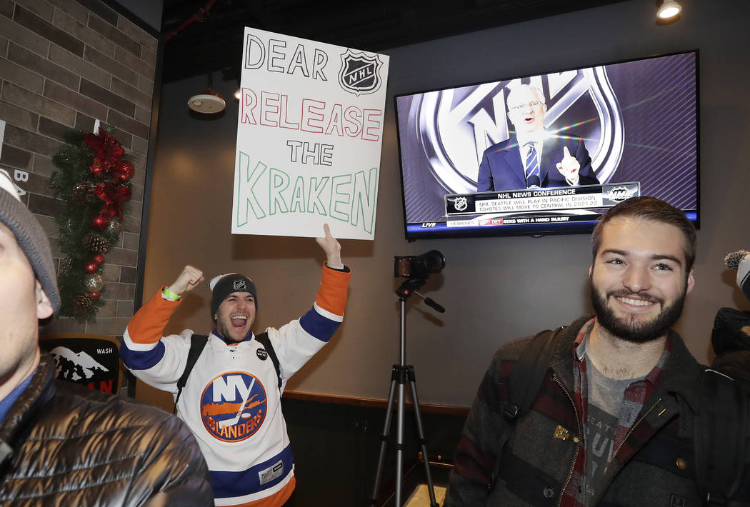 "Max Rubin cheers and holds a sign in favor of the team name ""Kraken"" following the announcement of a new NHL hockey team in Seattle, at a celebratory party Tuesday, Dec. 4, 2018, in Seat ..."