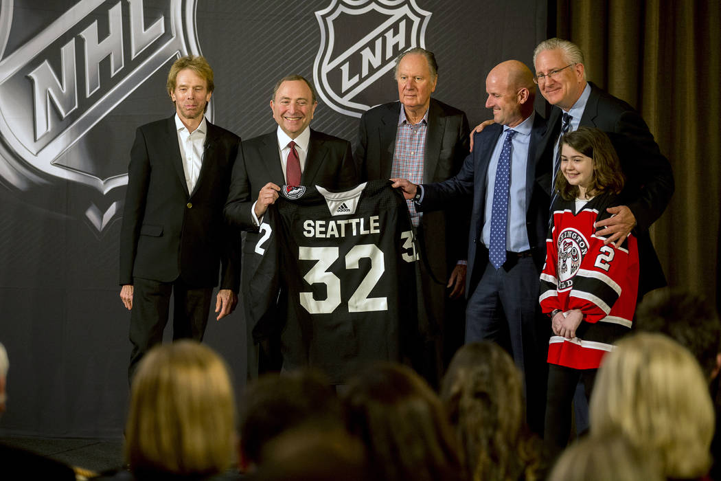 NHL commissioner Gary Bettman, center left, holds a jersey after the NHL Board of Governors announced Seattle as the league's 32nd franchise, Tuesday, Dec. 4, 2018, in Sea Island Ga.. Joining Bett ...