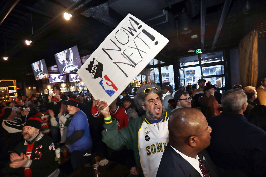 "Kris ""Sonic Guy"" Brannon holds up a sign in support of adding an NBA team following the announcement of a new NHL hockey team in Seattle, at a celebratory party Tuesday, Dec. 4, 2018, in ..."