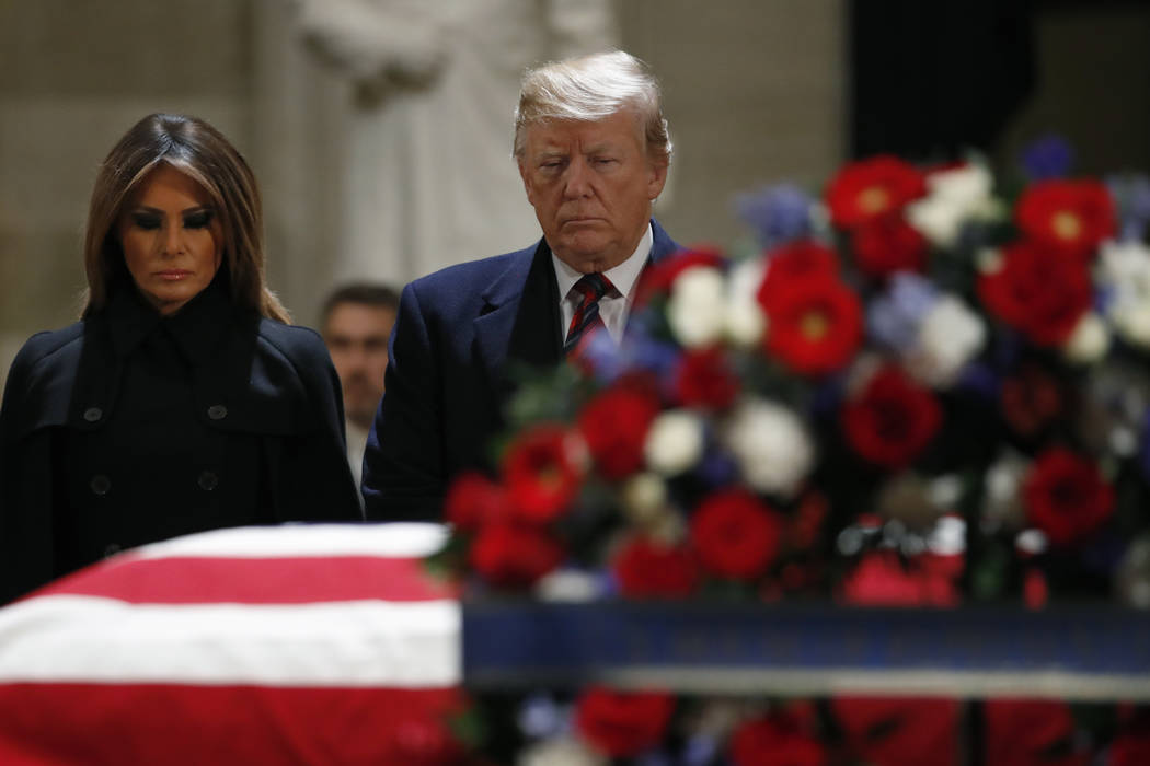 President Donald Trump and first lady Melania Trump pay their respects to former President George H. W. Bush, as he lies in state in the Rotunda of the U.S. Capitol, Monday, Dec. 3, 2018, in Washi ...