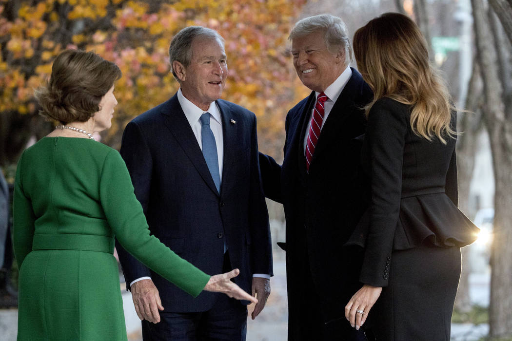 President Donald Trump and first lady Melania Trump are greeted by former President George Bush and former first lady Laura Bush outside the Blair House across the street from the White House in W ...